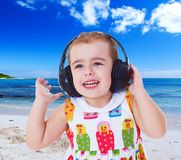Little girl listening to music on headphones. The concept of a happy childhood and a child's education Stock Image