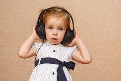 Little girl listening to music on headphones. Little cute girl listening to music with big headphones. That's funny Royalty Free Stock Photo