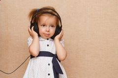 Little girl listening to music on headphones. Little cute girl listening to music with big headphones. Girl smiles and holding hands headphones Stock Image