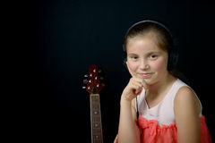 A little girl listening to music with headphones. And smile Stock Images