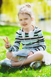 Little girl listening to music on headphones in a spring park outdoor.  Stock Image