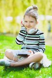 Little girl listening to music on headphones in a spring park outdoor.  Stock Photos