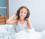 Little girl listening to music. At home in white bed Stock Photography