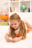 Little girl listening to music laying on the floor. In her room using earphones Royalty Free Stock Photo