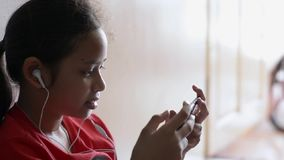 Little girl listening to music from mobile phone. Little girl listening to music from mobile phone with earphones at home