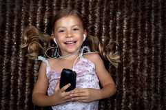 Little girl listening to music on an MP3 player. Pretty little girl lying on a rug and listening to music on an MP3 player Stock Images