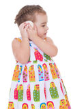 Little girl listening to seashell Stock Photo