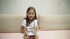 Little girl listens to music with headphones stock video