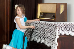 Little girl listens to old radio. Royalty Free Stock Photos