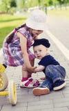 Little girl and little boy. Girl helps get the fallen boy Stock Image