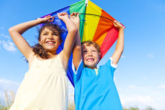 Little Girl And Little Boy Playing Kite Together Stock Photo