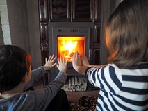 Children warm up. Little girl and little boy warm up by the fireplace royalty free stock image