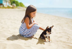 Little girl and little dog on the beach in sunny summer day. Near sea, child with puppy outdoors Stock Photos