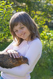 Little girl little farmer is holding a hen Royalty Free Stock Photo