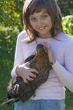 Little girl little farmer is holding a hen Royalty Free Stock Photos