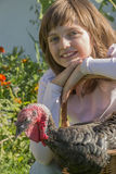 Little girl little farmer is holding a turkey Stock Photos