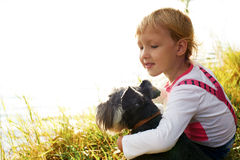 Little girl little girl hugging her dog. They look at the lake Royalty Free Stock Photo
