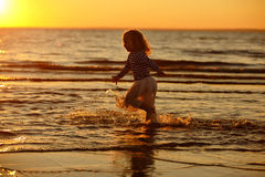Little girl little girl in a skirt and striped sweater runs thro Royalty Free Stock Photo
