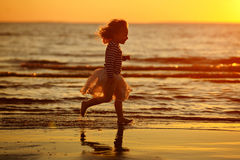 Little girl little girl in a skirt and striped sweater runs thro Royalty Free Stock Images
