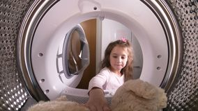 Little girl loading her stuffed toy to washing machine. View from the inside of washing machine stock video footage