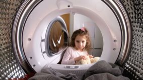 Little girl loading her stuffed toy to washing machine. View from the inside of washing machine stock video