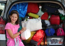 Little girl loads the bags in the trunk of her car Stock Photos