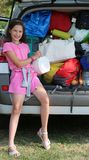 Little girl loads her purse in the car trunk Royalty Free Stock Images