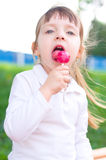 Little girl with lollipop. Happy little girl with lollipop outdoors Royalty Free Stock Photo