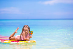 Little girl with lollipop have fun on surfboard in Stock Photo