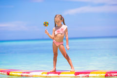 Little girl with lollipop have fun on surfboard in Stock Photography