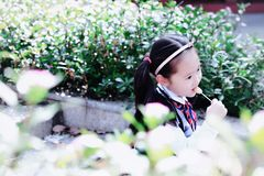 Little girl with lollipop. Sit on the steps in flower royalty free stock images