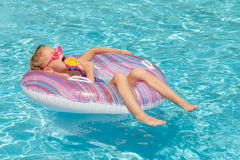 Little girl with lollipop lying on the  inflatable rubber circle Stock Photo