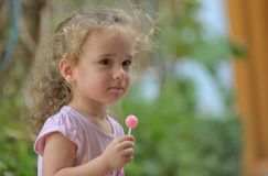 Little girl with lollipop. In nature stock image