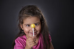 Little girl and lollipop Stock Images