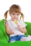 Little girl with  lollipop sit on green armchair Royalty Free Stock Photos