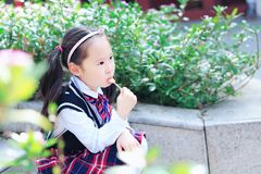 Little girl with lollipop. Sit on the steps in flower stock photo