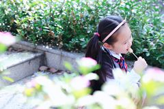 Little girl with lollipop. Sit on the steps in flower royalty free stock photos