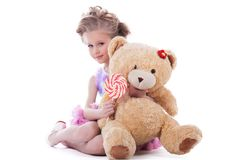 Little girl with lollipop and soft toy Stock Image