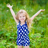 Little girl with long blond curly hair and raised hands Royalty Free Stock Images