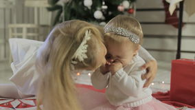 Little girl with long blond hair with her kid. Little wonderful girl with long blond hair with her baby sister near decorated Christmas tree stock video footage