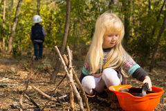Little girl with long blond hair playing outdoors Royalty Free Stock Images