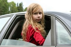 Little girl with long blond hair and in a red jacket looks through the open window of the car into the camera stock images