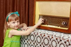The girl turns the volume knob on the old radio. Retro style. A little girl with long blond hair and a short bangs, in a short summer dress.The girl turns the Royalty Free Stock Images