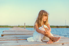 Little girl with long blond hair sitting on the pier Royalty Free Stock Photography