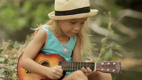 Little girl with long blond hair in straw hat stock footage