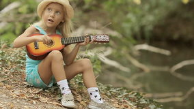 Little girl with long blond hair in straw hat. Playing guitar in the forest next to the river stock video