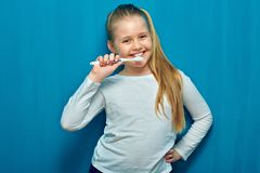 Little girl with long blonde hair cleaning teeth with toothy bru. Sh. Blue wall background Stock Photography