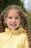 Little girl with long braids and missing a tooth outdoors in the Royalty Free Stock Images