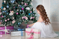 Little girl with long curled hair sitting near Christmas tree and gifts. Christmas time Royalty Free Stock Photos