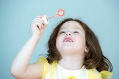 Little girl with long hair blowing bubbles